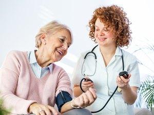 Young nurse measuring blood pressure of older woman.