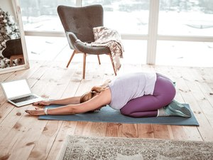 Woman in violet leggings doing 5-minute yoga routine for holiday anxiety