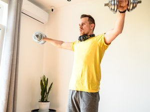 A young guy in sport wear is training at home