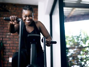 Black woman exercising on elliptical and smiling at home