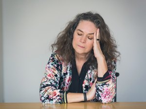 mature woman suffering with eyes closed at table