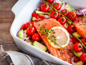 raw salmon with tomatoes, onion and lemon in white casserole dish
