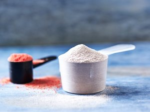 Scoop of Whey Protein and Creatine Powder. Sport nutrition. Rustic wooden background. Close up. Copy space