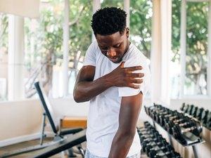 Sportsman holding shoulder that pops and cracks in gym