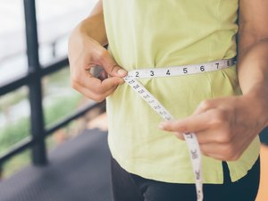 Midsection of Woman Measuring Her Waist With Tape Measure
