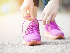 Young woman runner tying pink shoelaces