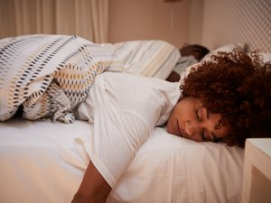 A young African-American woman asleep in bed, her partner in the background