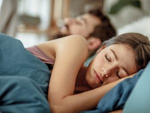 Woman sleeping with her husband in bed