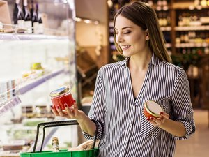Woman choosing jarred and canned foods at supermarket