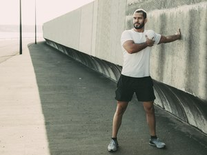Man doing range-of-motion exercises for his shoulders, stretching his arm across his chest