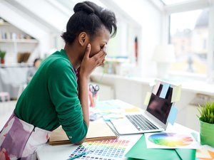 A woman sitting at her desk who is stressed from working too much