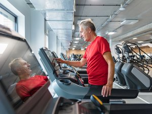 Senior man adjusting speed on treadmill, walking for an hour