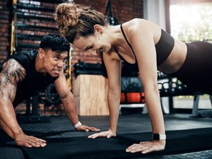 Woman holding plank with trainer