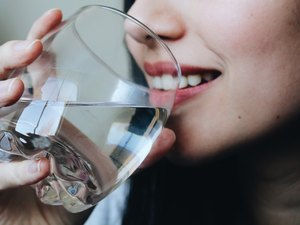 Close-Up Midsection Of Young Woman Drinking Water At Home