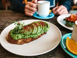 Sandwich or toast with avocado in the foreground. A person is going to eat it and drink coffee or tea