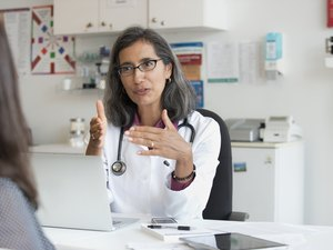 doctor wearing glasses and stethoscope talking to patient about pcos and fertility