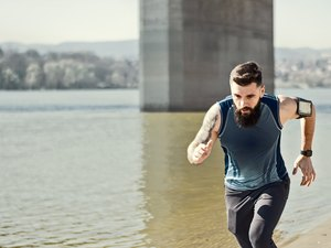 man running outdoors along a river in a virtual race