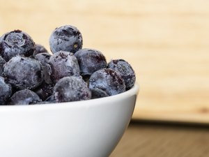 white bowl full of frozen blue berries