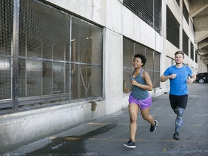 Couple running in city parking lot