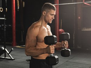 Young handsome bodybuilder during his arm workout in the gym