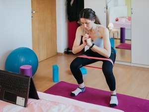 Woman performing squat with small looped resistance band