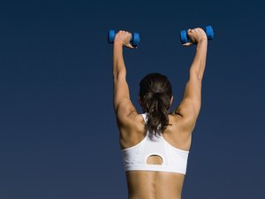 Rear view of mixed race woman holding dumbbells overhead