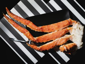 Crab legs and fork in black plate on black and white striped background, view from above