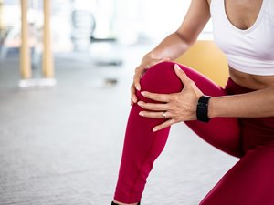 Close up of young fit and active woman with knee pain