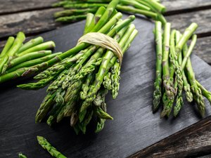 Fresh raw green Asparagus on wooden chopping board