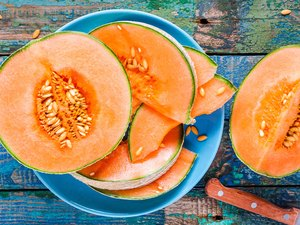 Foods high in potassium like melon on a plate on a rustic background