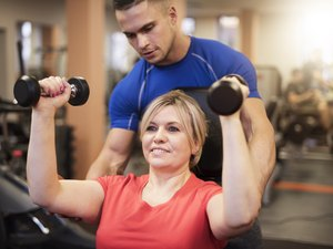 Woman doing shoulder exercise with a trainer during a beginner strength-training workout