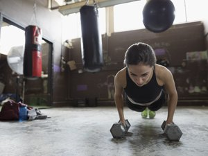 Strong female boxer doing push up exercise with dumbbells at gym