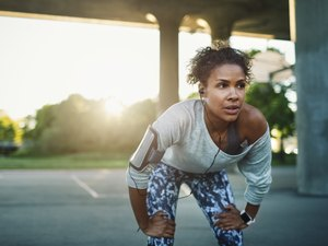 Fit woman taking a break from exercise due to heartburn