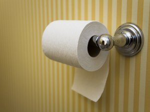Toilet paper roll hanging in a bathroom with striped yellow wallpaper