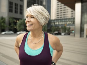 Smiling, confident athletic mature woman on city street