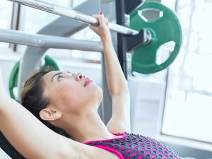 Female fitness instructor working out, doing incline bench press in health club