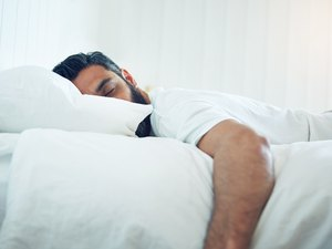 A man sleeping in bed to support his immune system