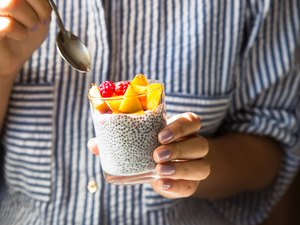 An unrecognizable woman eating chia seed pudding with raspberries and peaches in a glass jar