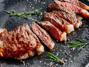 Grilled sliced beef steak with rosemary close up