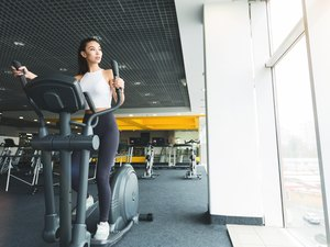 Woman exercising on cross trainer near panoramic window