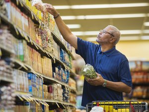 man shopping in grocery store reading ingredient list