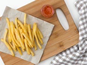 French fried potatoes on cutting board with sauce top view.