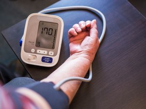 Senior woman measures high blood pressure at home