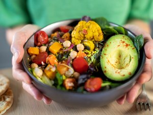 Close Up Of Woman Eating Healthy Vegan Meal In Bowl
