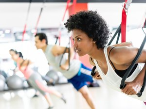 Beautiful black woman doing workouts with suspension straps at the gym