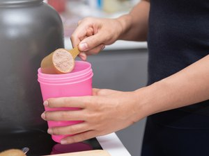 Healthy women preparing a whey protein after doing weight training in the kitchen.