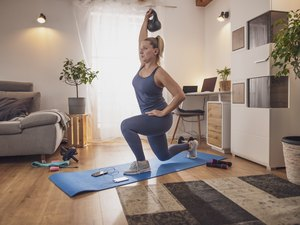 woman lunging with kettlebell on a blue yoga mat in living room