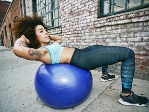 Hispanic woman balancing on fitness ball near brick wall