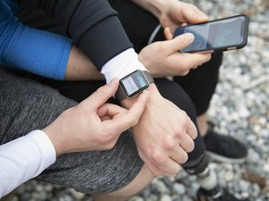 People preparing smart watch, checking fitness app on smart phone
