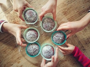 Group of people taking cupcakes with erythritol off a table